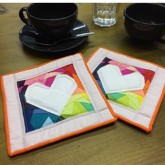 Two Rainbow heart coasters that are rainbow inspired with an orange border