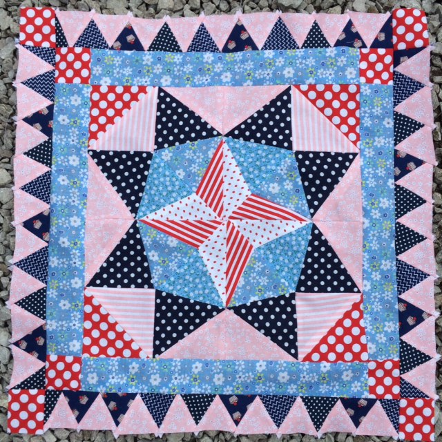 a 4 point star surrouned by an 8 point star and two blue pink borders