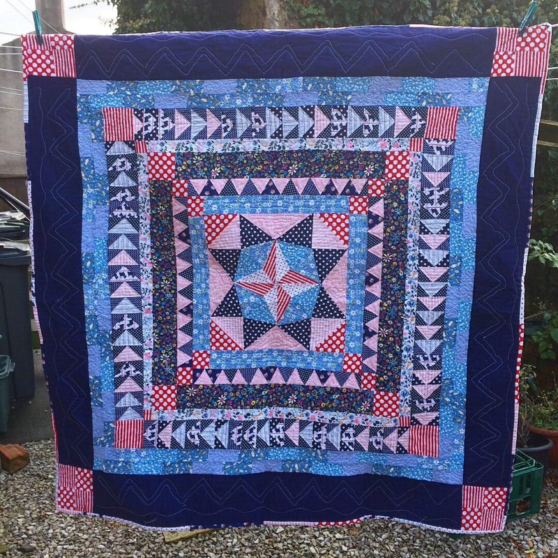 Marcelle Medallion quilt in blue, pink and red, a circle of squares getting larger and largermaking a beautiful patchwork quilt