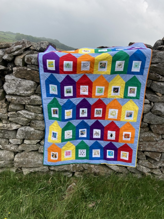 The stay at home polaroid quilt resting on a drystone wall