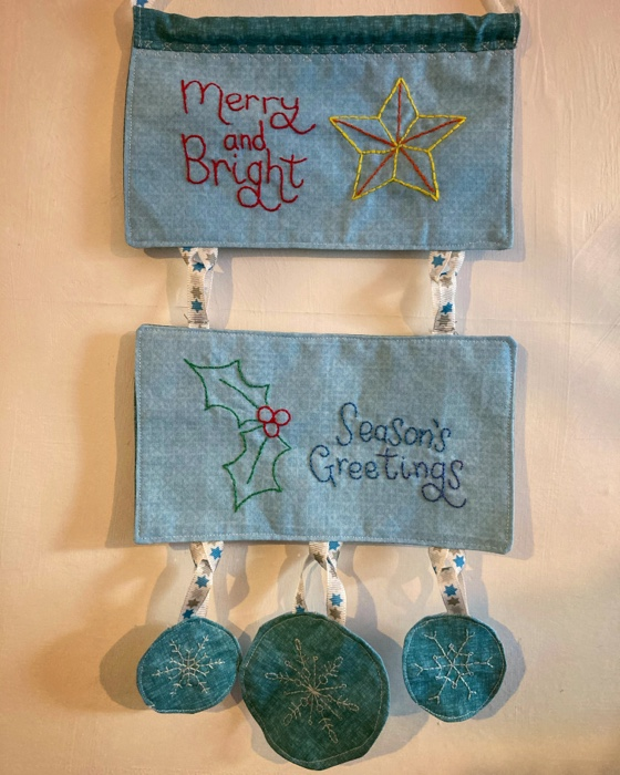 Hanging banner that says Merry and Bright with a yellow star and Seasons greetins with some holly and 3 little snow flakes hanging from the bottom