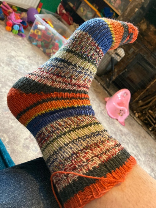 a stripey orange white flecks and blue loom knit sock on my foot, there is a pink potty in the back ground that makes for amusing photograpy