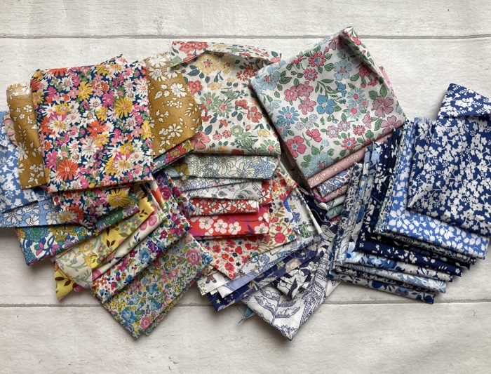 A small pile of Liberty Floral Fabrics in a variety of colour